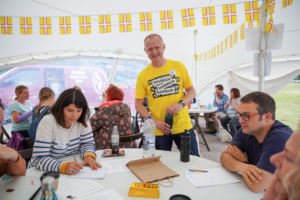 Alan in the Comms Unplugged tent with bright yellow not worrier / warrior message emblazoned on the front. Unpluggers at a table getting involved in the activity.
