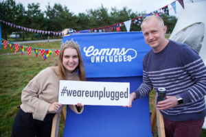 Lauren and Alan sharing a smile at Comms Unplugged. Tent and bunting in the background holding a blue #weareunplugged sign board.